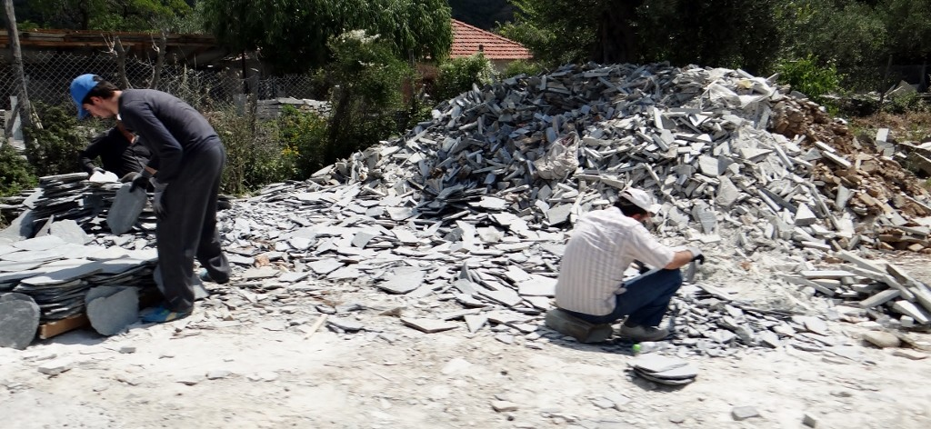 Three men at the roadside chipping away at a pile of slate offcuts to make some tiles.